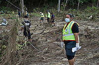 Police officers and volunteers search through debris for missing persons along the coast that bore the full force of the tsunami. More than 170 people died when a tsunami triggered by an 8.3 magnitude earthquake hit Samoa and neighbouring Pacific islands on 29/09/2009. Samoa (formerly known as Western Samoa)..