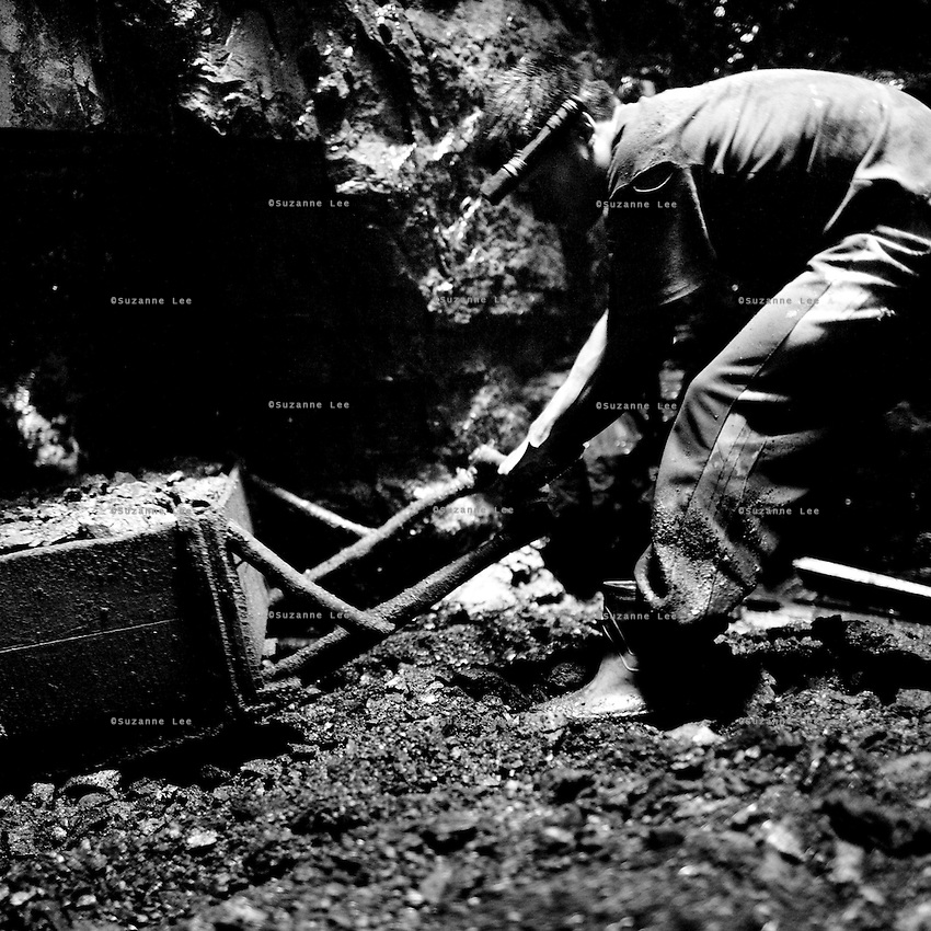 A young miner pulls a cartful of coal out from the 'rat holes'. Small sized miners are used to work in the 'rat holes' because they can fit in the tunnels which have an average diameter of 2 feet. The miners work from 7am to 1pm and from 2pm to 7pm and sometimes later. ..In Jaintia Hills, underaged children work in unscientific, largely unmonitored and extremely dangerous underground coal mines dug out by often trafficked children using primitive methods and tools. The north eastern Indian state of Meghalaya sits on about 640 million tons of coal, with 40 million tons of that in Jaintia Hills alone which has about 5000 privately owned mines.  Photo by Suzanne Lee for Panos London