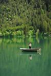 Fisherman in boat reflected in Lake Plansee near Reutte, Austrian Alps. Austria.