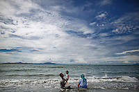 """A Muslim family enjoys nice weather on the beach in Banda Aceh December 11, 2012. Indonesia is the world's most populous Muslim nation, but nowhere is the faith more strictly interpreted than in Aceh, sometimes referred to as the """"verandah of Mecca"""" because it was one of the first parts of the archipelago to turn to Islam. Aceh is Indonesia's only province to have implemented Sharia or Islamic laws.    REUTERS/Damir Sagolj (INDONESIA)"""