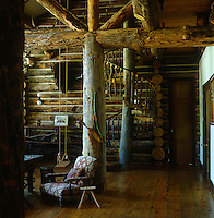 The living room of this log cabin has enormous log cross beams, a wooden spiral staircase and an indoor swing