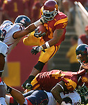 USC's LenDale White jumps over Arizona defenders while Arizona's #49 Copeland Bryan pulls him down on Saturday, October 8, 2005 at the Los Angeles Memorial Coliseum. USC defeated the Azcats 42-21.