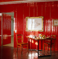 The lacquered red tongue and groove walls and black mosaic floor of this kitchen/diner are complimented by a copper-topped table
