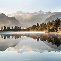 Sunrise over Lake Matheson and Southern Alps, with Mt. Tasman and Mt. Cook on horizon, Westland Tai Poutini National Park, West Coast, South Westland, UNESCO World Heritage Area, New Zealand, NZ