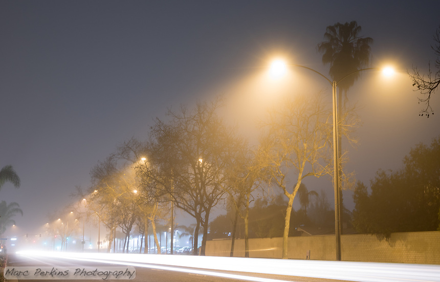 Fog obscures the trees and streetlights of Harbor Blvd. in Costa Mesa, CA in this long-exposure night image.  A single car drives past the camera, creating a long white streak that frames the bottom of the image.
