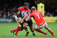 Ben Tapuai of Bath Rugby is double-tackled by Maro Itoje and Schalk Burger of Saracens. Aviva Premiership match, between Bath Rugby and Saracens on December 3, 2016 at the Recreation Ground in Bath, England. Photo by: Patrick Khachfe / Onside Images