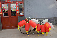 In a small hutong, alleyway, of Shichahai area a bike is covered in lanterns in front of a restaurant in Beijing,China.