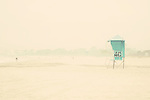 a lone person &amp; a lifeguard tower stand out against the backdrop of fog on a california beach