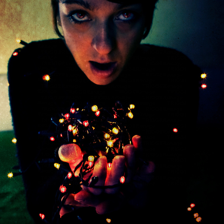 a young woman holding a handful of christmas lights