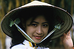 Mai Tku Ka, a guide, wears a traditional cone hat made of bamboo in Hanoi, North Vietnam.  (Jim Bryant Photo)....