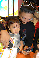 A man and a young boy play a mobile phone game together on the booth of Japanese mobile phone carrier, AU.