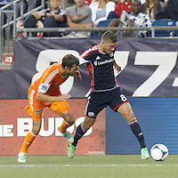 New England Revolution defender Chris Tierney (8) dribbles down the wing as Houston Dynamo forward Cam Weaver (15) defends. In a Major League Soccer (MLS) match, Houston Dynamo (orange) defeated the New England Revolution (blue), 2-1, at Gillette Stadium on July 13, 2013.