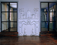 A pair of glass doors flanks a cartoon-style plaster relief of a fireplace in this living room