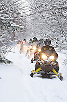 A group of snowmobilers travel up a narrow trail through deep lake effect snow near Lake Linden Michigan during a tour of Michigan's Upper Peninsula.