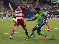 Obafemi Martins, left, of Seattle Sounders FC kicks the ball past Matt Hedges of FC Dallas at CenturyLink Field in Seattle Saturday August, 3, 2013. The Sounders defeated Dallas 3-0.
