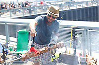 BROOKLYN, NY - SEPTEMBER 6, 2014: A cook from Ovelia bastes pork, while it roasts on a spit. Ovelia was one of dozens of restaurants that participated in Pig Island at Erie Basin Park in Red Hook. CREDIT: Clay Williams.<br /> <br /> <br /> &copy; Clay Williams / http://claywilliamsphoto.com