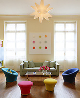 Colourful contemporary chairs and stools in this living room are arranged like pieces of sculpture on the dark burnished wood of the floor