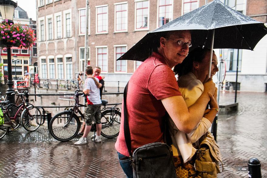 Nederland, Utrecht, 20 juli  2014<br /> Regen. Mensen op straat met en zonder paraplu in de regen <br /> Foto (c) Michiel Wijnbergh