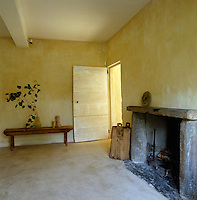 Massive stone slabs form a simple fire surround in this spacious under-furnished room with plaster walls
