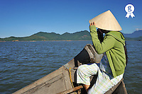 Woman (16) holding conical hat on boat (Licence this image exclusively with Getty: http://www.gettyimages.com/detail/83154203 )