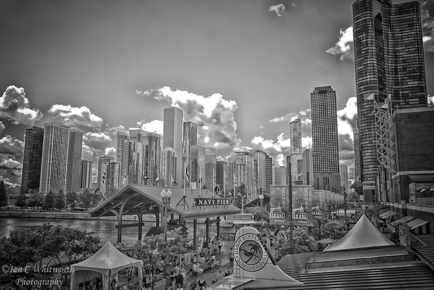 Looking across the top of Navy Pier in black and white with the city of Chicago in the background.