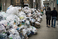 Pedestrians walk past bags of recyclable trash awaiting pick-up in the Chelsea neighborhood of New York on Saturday, March 18, 2017. As the snow melts from out recent storm the Dept. of Sanitation is starting to resume trash collection.  (© Richard B. Levine)