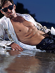 Young man wearing unbuttoned wet and dirty shirt lying on a sea shore at dusk