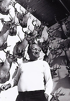 Rancher and hunter shows his deer head collection in San Diego, Texas.  1996