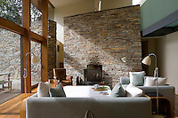 Natural materials are a feature of the house and in the living room the large stone fireplace echoes the garden wall outside