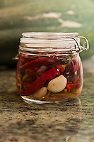 A jar of preserved cayenne peppers and garlic.