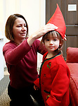 "Washington, CT- 29 December 2013-122913CM15  CL ONLY PLEASE----  Cara Abraham, of Washington helps her daughter, Darya, 2, into costume before the start of a miniature procession of Sankta Lucia, inside the Gunn Memorial Library in Washington on Sunday.  Darya portrayed ""Tomte"" in the processional.  Christopher Massa Republican-American"