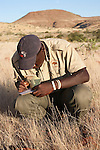 Save the Rhino Trust tracker Dansiekie Ganaseb, recording black rhino sighting, Palmwag concession, Kunene region, Namibia