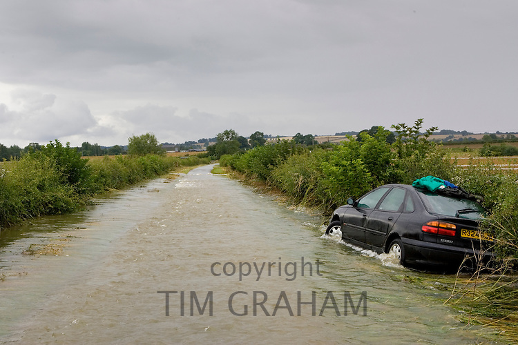 Car forced off the road by flood water sweeping from field to field in Lyneham, Oxfordshire, England, United Kingdom