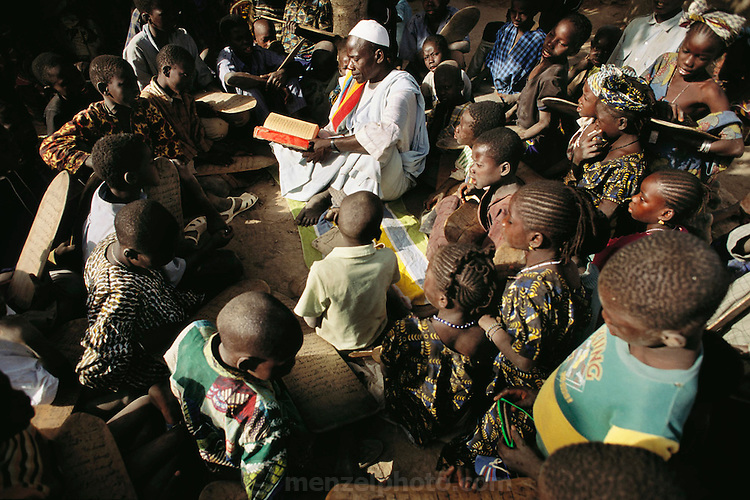 "The Imam of Kouakourou village in Mali teaches a Koranic lesson to students. Several of Soumana Natomo's children attend these classes, along with classes at what they call, ""the modern school"" taught in French, where they learn math and reading. The Natomo family lives in two mud brick houses in the village of Kouakourou, Mali, on the banks of the Niger River. Material World Project."