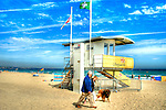 A beach watch tower people walking dog on beach