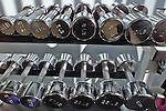 Shiny chrome dumbells in a home gym environment in San Francisco California.
