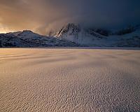Winter sunrise over frozen lake Storvatnet, Flakstadøy, Lofoten Islands, Norway