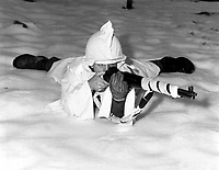 Sergt. (or T4c.) Marvin E. Eans, Jr., demonstrates the new snow cape being used by First U.S. Army Infantrymen in snow-covered areas in Belgium.  White rags are wrapped around his rifle for additional camouflage. St. Vith. December 15, 1944. T5c. Richard A. Massenge. (Army)<br /> NARA FILE #:  111-SC-197455<br /> WAR &amp; CONFLICT BOOK #:  1069