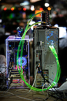 Computer with fancy cooloing system. One of the world's largest convention of computer enthusiasts, simply called 'The Gathering'. Over five thousand young people come together each Easter, some travelling long distances, each carrying their own computer equipment to the massive Vikingship sports hall in the city of Hamar. The main activity is online gaming. Many hardly see daylight or taste fresh air for the entire five days as they compete with their fellow geeks for cash prizes and the honour of being the best.