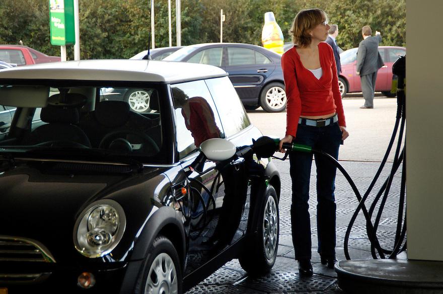 Nederland, Woerden, 1 nov 2005.Benzine tanken, diesel tanken..Mensen tanken bij benzinepomp langs de snelweg. .Vooral diesel geeft extra veel vervuiling en milieunadelen vanwege uitstoot van roet deeltjes, zgn. fijn stof. .dieselrijders.mobiliteit, verkeer.Foto (c) Michiel Wijnbergh