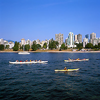 Vancouver, BC, British Columbia, Canada - Recreational Sea Kayaking and Canoeing in English Bay, West End of Vancouver Skyline and Sunset Beach in background