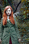 A girl wearing a green coat, standing in the forest.