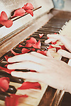 woman playing the piano with red petals on the keys