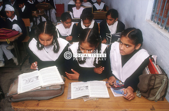 School girls and boys sitting at desks reading books in senior secondary modern school; Punjabi University; Patiala; Punjab; India,
