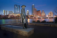 An Austin treasure, the majestic Stevie Ray Vaughan Memorial Statue stands affront the beaconing downtown Austin Skyline at Sunset