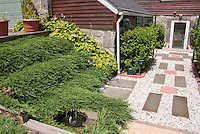 Entrance to house made more appealing with simple stone path and tier of plants and shrubs, Juniper & hosta groundcovers over hill slope