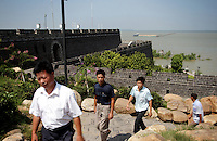 Men walking near Dongting Lake, Hunan Province. Dongting Lake has decreased in size in recent decades as a result of land reclamation and damming of the Yangtze. China. 2010