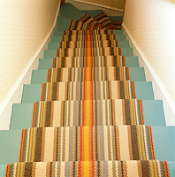 View down the wooden staircase which is painted a light blue and covered in a striped runner