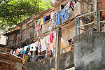 Woman hangs laundry above Rua Aroma de Rosas.