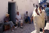 Tunisia, citt&agrave; di Kairouan, donne e uomini in abiti tradizionali in una strada della Medina.<br /> Tunisia, the city of Kairouan, women and men in traditional clothes in a street in the Medina.